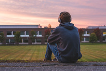Teenager Sitting Alone At The Top Of A Hill At Sunset. He Is Listening To Music Through His Headphones.