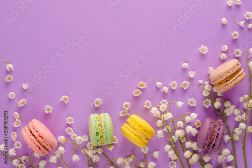 Poster Muguet de mai Colorful macaroons decorated with blooming lily of the valley on purple background. Sweet french dessert concept. Frame composition. Flat lay. Space for text. Greeting card concept