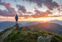 Man Watching Dramatic Sunset In The Mountains