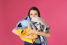 Young Woman Holding Pile Of Dirty Laundry On Color Background