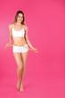 Leinwandbild Motiv Slim woman measuring her waist on color background, space for text. Perfect body