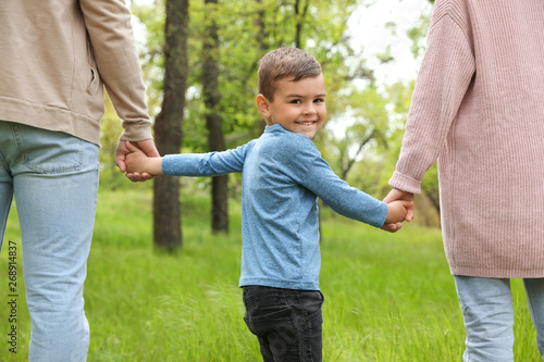 Obraz Happy little child holding hands with his parents in park. Family weekend - fototapety do salonu