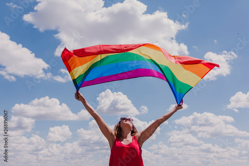 Woman holding the Gay Rainbow Flag over blue and cloudy sky outdoors. Happiness, freedom and love concept for same sex couples. LIfestyle outdoors