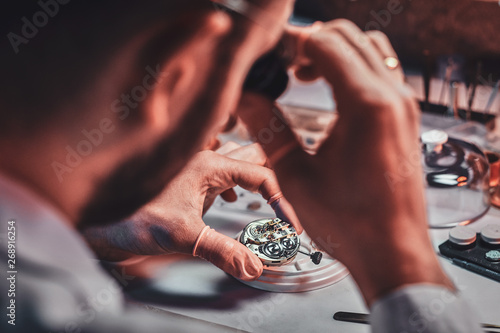 Fotografía  Mature clockmaster is fixing old watch for a customer at his busy repairing workshop