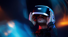 Model Young Man With Beard In Glasses Of Virtual Reality. Augmented Reality,  Future Technology Concept. VR. Neon Light.