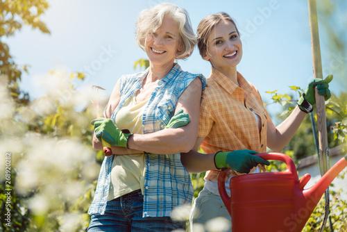 Mutter und erwachsene Tochter haben Spaß bei der Gartenarbeit Fototapet