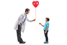 Male Doctor Giving A Red Heart Balloon To A Little Boy