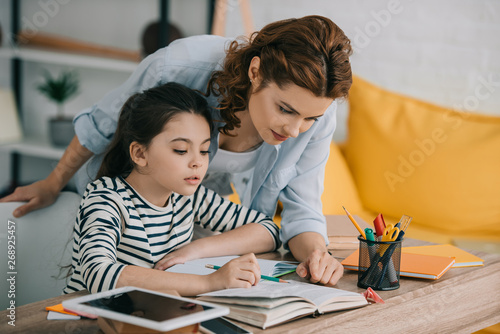 attentive mother helping adorable daughter doing schoolwork at home Tapéta, Fotótapéta