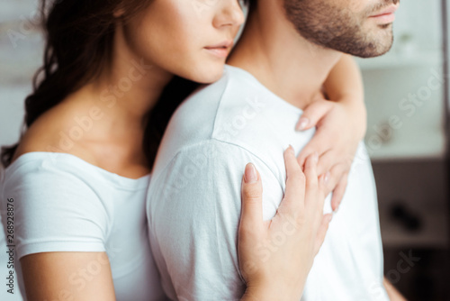 cropped view of woman embracing boyfriend at home Fototapeta