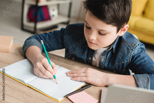 cute attentive boy writing in notebook while sitting at desk and doing homework