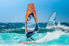 Water Sports: Windsurfers Riding Waves With Colored Sails In Oceanic Blue Water