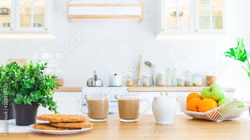 Two cups of morning coffee, cookies and fruit on the kitchen table Wallpaper Mural