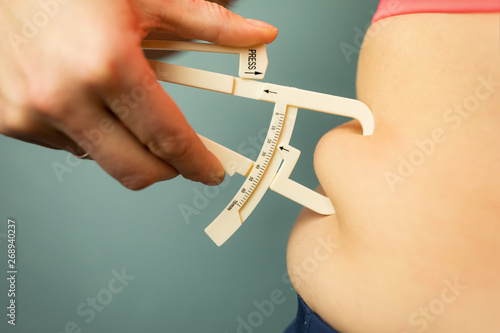 Leinwand Poster Woman measuring her body fat with caliper