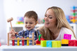Leinwandbild Motiv Mom or teacher playng with kid toddler in nursery. Educational toys for children.