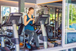 Young woman using phone while training at the gym. Woman sitting on exercising machine holding mobile phone