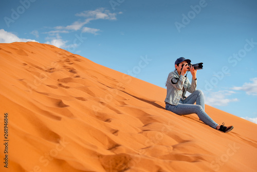 Foto auf Gartenposter Rotglühen Young Asian woman traveler and photographer holding camera taking photo while sitting on sand dune in Namib desert of Namibia, Africa. Travel photography concept