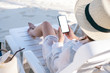 Leinwandbild Motiv Mockup image of a woman holding black mobile phone with blank desktop screen while laying down on beach chair on the beach