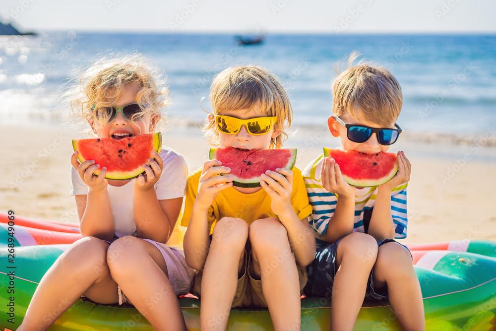 Fototapety, obrazy: Children eat watermelon on the beach in sunglasses