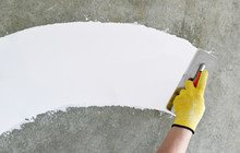 Hand With A Spatula, The Process Of Applying A Layer Of Putty. Renovation Of Apartments. Repair The Walls. Free Space For Advertising, Text.