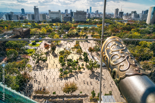 Fotografía  View from the rooftop of Osaka Castle with people down at the Castle Park in autumn in the foreground and Osaka Skyline in the background in Kansai region, Japan