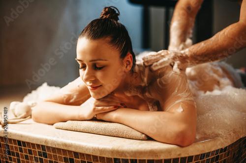 Fotografija  Pretty dark haired female having relaxing massage with foam in a wellness spa turkish hammam