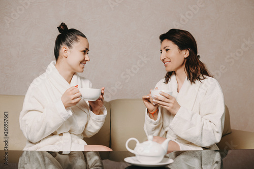 Fotografija Side view portrait of two lovely woman talking with a cup of tea in their hands after spa procedures dressed in bathrobe in a wellness spa center
