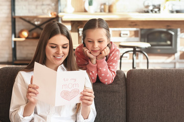 Happy mother receiving greeting card from her little daughter at home