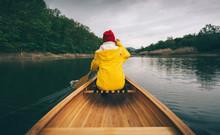 Rainy Day Boat Ride. Rear View Of Woman In Yellow Raincoat Paddling Canoe