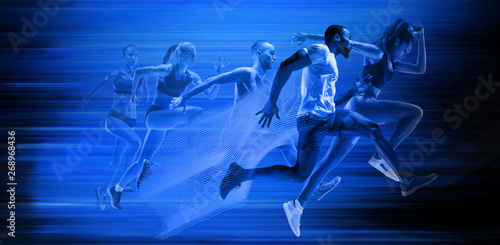 Fotografie, Obraz  Young african-american and caucasian men and women running isolated on blue studio background