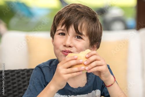 Fototapeta child eating a hamburger obraz