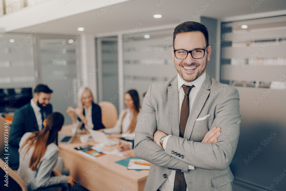 Fototapeta Handsome smiling businessman in formal wear and eyeglasses standing at boardroom with arms crossed. Love and respect do not automatically accompany a position of leadership. They must be earned
