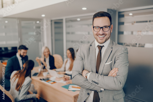 Foto Handsome smiling businessman in formal wear and eyeglasses standing at boardroom with arms crossed