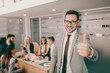 Handsome Caucasian businessman in formal wear and eyeglasses giving thumbs up while standing in boardroom. Every job is a self-portrait of the person who does it. Autograph your work with excellence.
