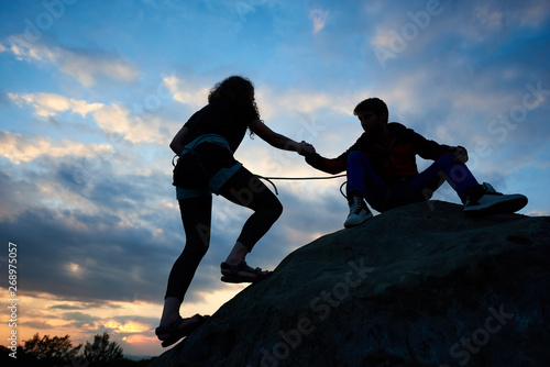 Woman is climbing on cliff. Man friendly hand helping her. Bouldering on the mountains in the evening. Silhouette of slim young woman outdoors in summer on beautiful sky background. Teamwork concept.