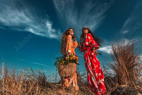 Photo  two beautiful stylish boho models outdoors