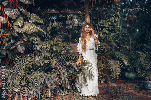 Canvas Print beautiful young cheerful boho style woman at tropical green leaves background