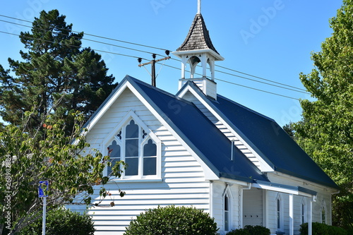 Photo  Wooden Anglican church of St Leonard in Matakana with bright white cladding and blue roof