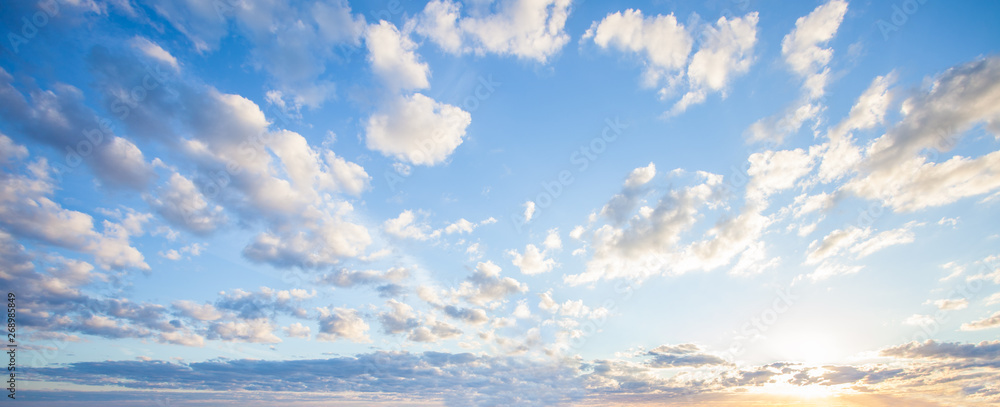 Fototapeta Blue sky clouds background. Beautiful landscape with clouds and orange sun on sky