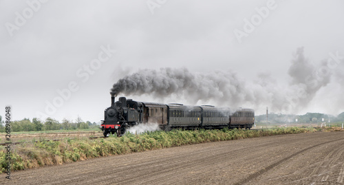 Fototapeta Vintage steam train with ancient locomotive and old carriages runs on the tracks in the countryside obraz na płótnie