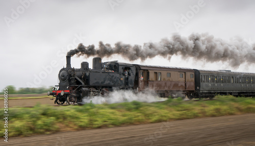 Fotomural  Vintage steam train with ancient locomotive and old carriages runs on the tracks