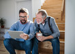 canvas print picture An adult son and senior father with tablet sitting on stairs indoors at home.