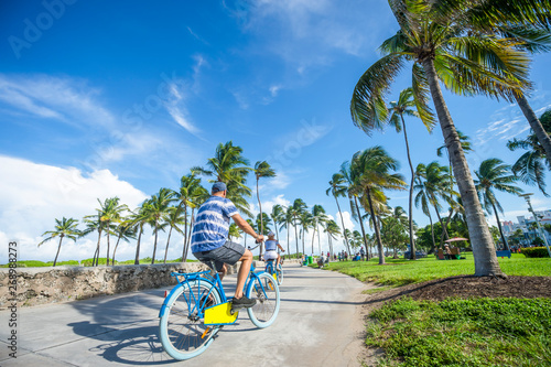 Photo Tourists ride bicycles along the beachfront promenade in Lummus Park adjacent to