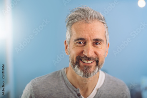 Obraz na plátně  happy middle aged gray haired bearded man smiling against blue background
