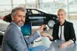 car agent handing the car keys to customer in car dealership showroom