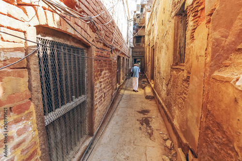 Varanasi narrow alleyway with old residential buildings. Varanasi is known as the oldest city of India with ancient architecture and historic temples