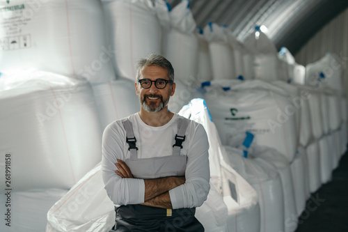 agribusiness worker standing crossed arms in front of seeds in warehouse Wallpaper Mural