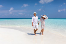 Happy Couple Walks Down A Trop...