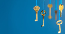 Many Old Keys Of Yellow Gold Color Are Hanging On Thread On A Blue Background. The Concept Of The Selection Of Access Or Password To The Secret Data. Copy Space For Text.