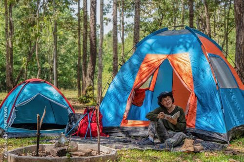 male sitting in front of camping tent in camping activity in forest Canvas