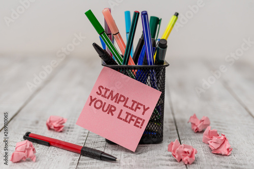 Obraz Conceptual hand writing showing Simplify Your Life. Concept meaning focused on important and let someone else worry about less ones Writing equipment and paper scrap with blank sheets on wooden desk - fototapety do salonu